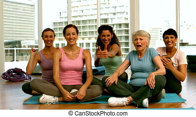 Group of women in fitness studio showing thumbs up in slow...