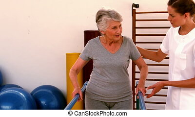 Physiotherapist helping patient walk with parallel bars in...