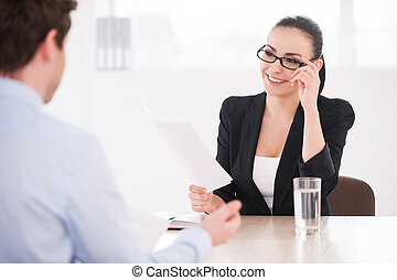 Interviewing a job candidate. Cheerful young woman in formalwear holding document and smiling while man sitting in front of her and gesturing