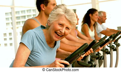 Happy spinning class in fitness studio in slow motion