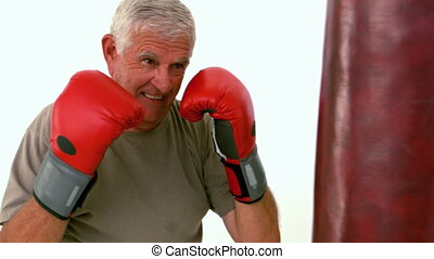 Old man hitting a punching bag in slow motion