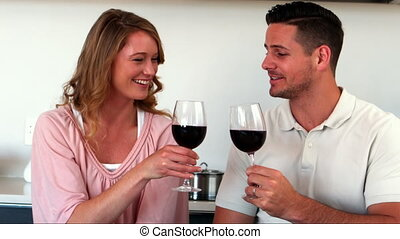 Happy couple having red wine in kitchen