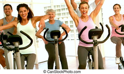 Happy spinning class cheering in slow motion