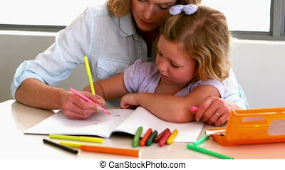 Mother coloring with daughter at table - Mother colouring...