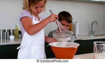 Siblings sieving flour into a bowl in slow motion