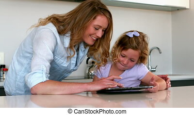Mother using tablet with her daughter in the kitchen in slow...
