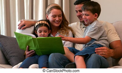 Happy young family looking at photo album together in slow...
