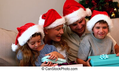 Happy young family opening Christmas presents - Happy young...