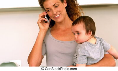 Mother holding her baby son in the kitchen talking on phone...