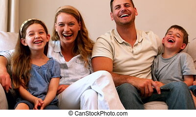 Happy young family laughing on couch in slow motion