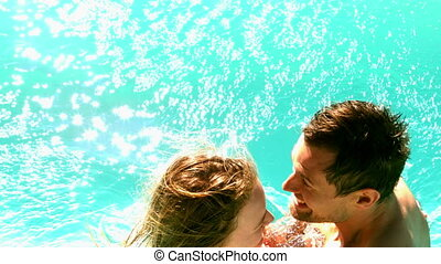 Sexy couple dunking in the pool together on holidays in slow...