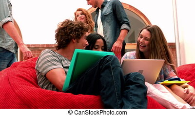 Happy students relaxing in common room in slow motion