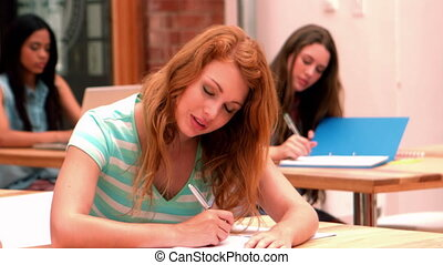 Happy student sitting at desk smiling at camera in slow...