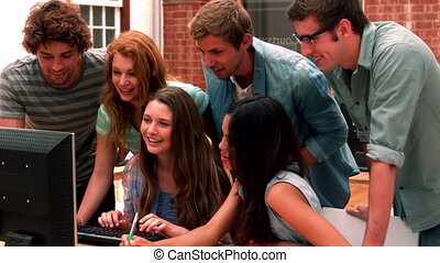 Happy students looking at computer