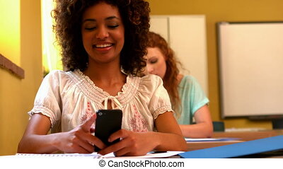 Pretty student sending a text in class - Pretty student...