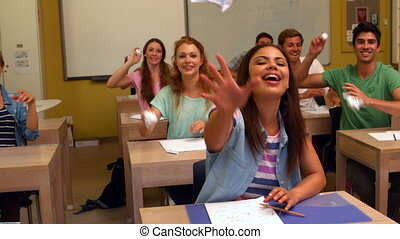 Laughing students throwing paper in classroom in slow motion
