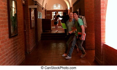 Happy students running through a hall