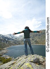 woman greeting big lagoon - duke lagoon at gredos mountains...