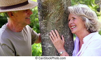 Retired couple leaning against tree smiling at each other at...