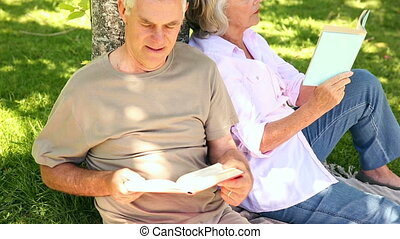 Retired couple leaning against tree