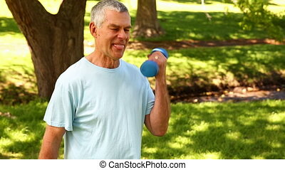 Retired man lifting weights outside on a sunny day