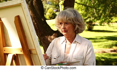 Retired woman painting outside