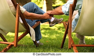 Retired couple sitting in deck chairs holding hands on a...