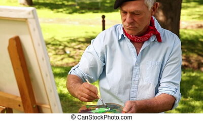 Retired man painting outside on a sunny day