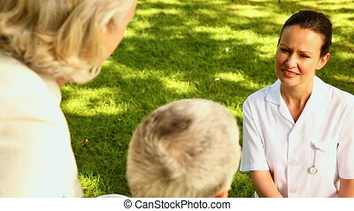 Nurse talking to man in wheelchair with his wife on a sunny...