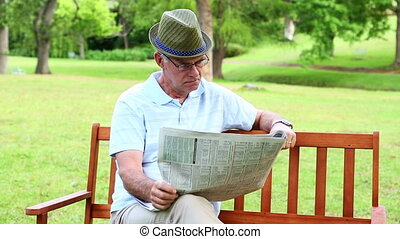 Retired man reading the paper on a bench