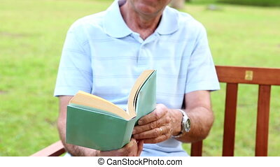 Retired man reading on a park bench