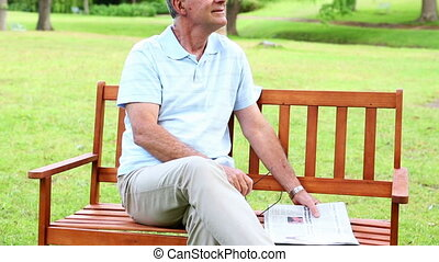 Retired man relaxing with the paper on a park bench on a...