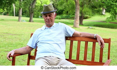 Retired man dozing on a park bench on a sunny day