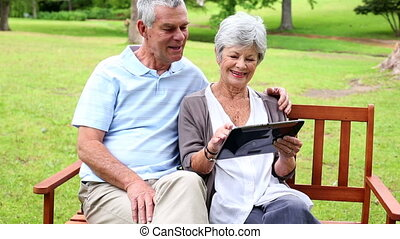 Retired couple sitting on a park bench using a tablet on a...
