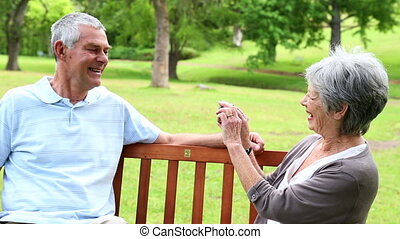 Retired couple sitting on a park bench taking a picture on a...