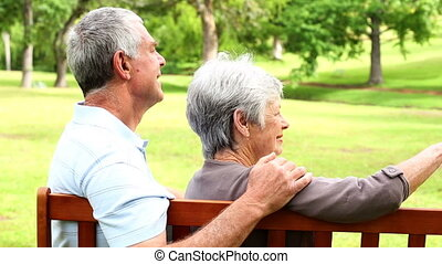 Retired couple sitting on a park bench together on a sunny...