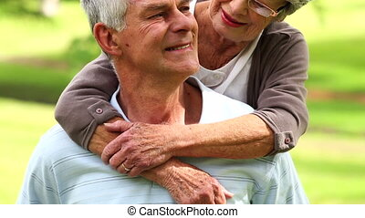 Affectionate senior couple in the park hugging on a sunny...