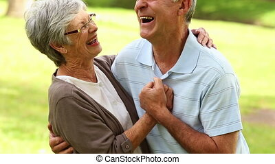 Retired couple in the park hugging
