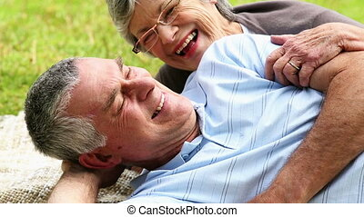 Affectionate senior couple relaxing in the park lying on...