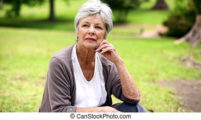 Upset senior woman sitting in the park