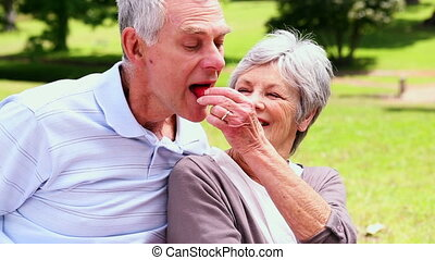 Senior woman feeding her husband a strawberry