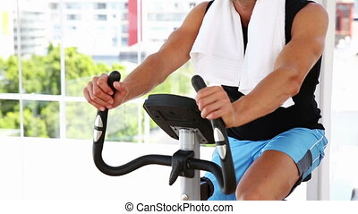 Fit man working out on exercise bike at the gym