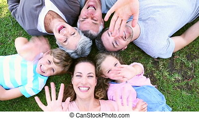 Extended family lying in the park together smiling up at...