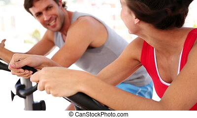 Fit couple working out on exercise bikes