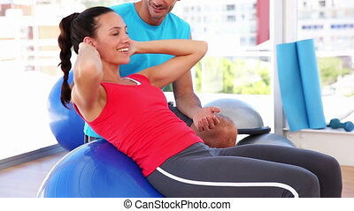 Fit woman doing sit ups on blue exercise ball with trainer...