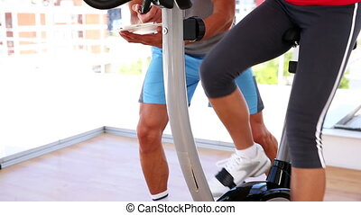 Fit woman working out on exercise bike with her trainer