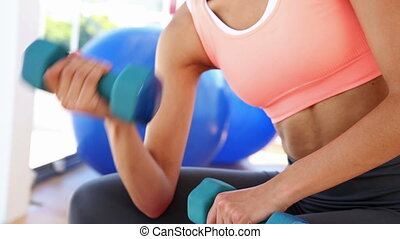 Fit woman lifting dumbbells and smiling at camera at the gym...