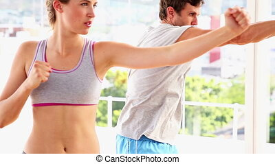 Fit couple punching together at the gym