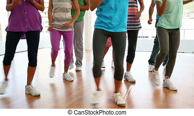 Zumba class dancing in studio at he gym