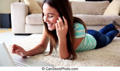 Pretty brunette relaxing on the rug using laptop talking on...